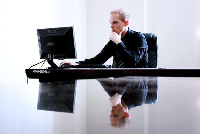 Przykład darmowej fotografii pochodzącej z banku zdjęć. Zdjęcie przedstawia człowieka przy komputerze, prawdopodobnie księgowego.